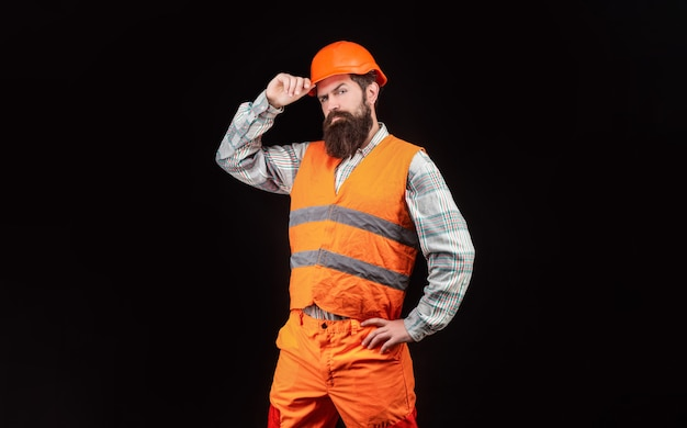 헬멧에 단단한 모자, 감독 또는 수리공을 쓴 빌더. 헬멧이나 단단한 모자를 쓰고 있는 수염난 남자 노동자. 빌더의 초상화입니다. 건설 유니폼을 입은 노동자. 남자 건축업자, 산업.