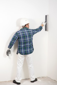 퍼티 나이프로 흰 벽을 석고 안전 헬멧에 빌더