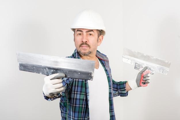 흰 벽에 두 개의 퍼티 나이프와 안전 헬멧에 작성기