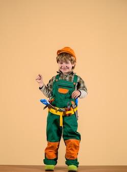 Builder kid playing with repair tools kid as construction worker repair concept little boy in helmet