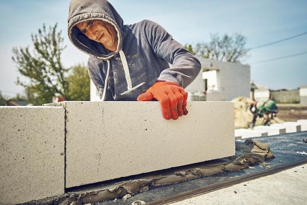 Строитель кладет газобетонный блок на строительной площадке