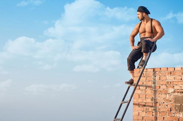 Строитель, опираясь на кирпичную стену на высоком