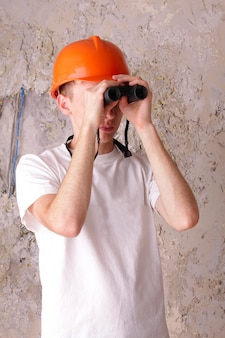 Builder looking through binoculars at the of the plastered walls
