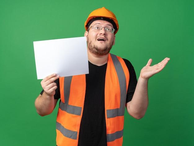 Uomo del costruttore in giubbotto da costruzione e casco di sicurezza che tiene una pagina vuota che guarda in alto felice e allegro in piedi su sfondo verde
