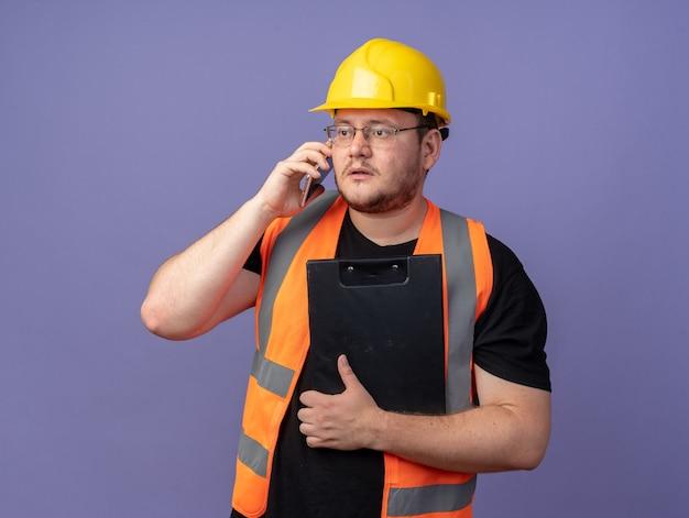 Uomo costruttore in giubbotto da costruzione e casco di sicurezza che tiene appunti guardando da parte con una faccia seria mentre parla al telefono cellulare in piedi su sfondo blu
