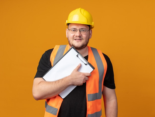 Builder man in construction vest and safety helmet holding clipboard looking at camera