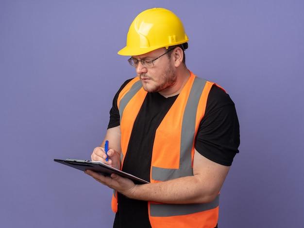 Uomo del costruttore in giubbotto da costruzione e casco di sicurezza che tiene appunti scrivendo qualcosa con la penna che sembra sicuro in piedi su sfondo blu