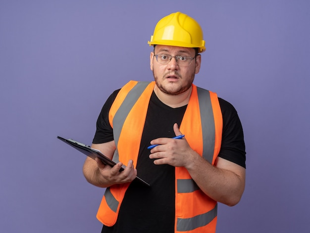 Builder man in construction vest and safety helmet holding clipborad and pen looking at camera amazed and surprised standing over blue