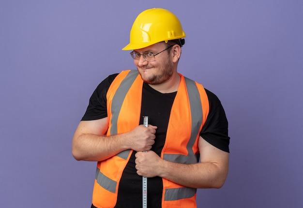 Uomo del costruttore in giubbotto da costruzione e casco di sicurezza che tiene il metro a nastro guardando la telecamera sorridendo sornione