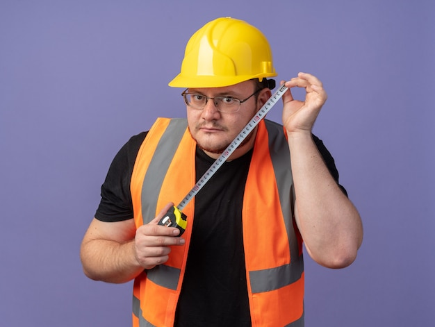 Builder man in construction vest and safety helmet holding measure tape looking at camera surprised