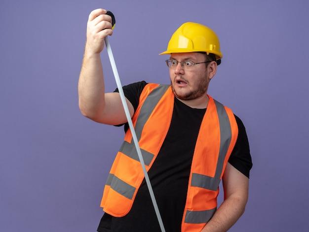 Uomo costruttore in giubbotto da costruzione e casco di sicurezza che tiene il metro a nastro guardandolo stupito e sorpreso