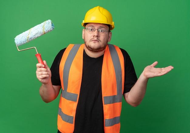 Uomo del costruttore in giubbotto da costruzione e casco di sicurezza che tiene il rullo di vernice guardando la telecamera confusa alzando le spalle