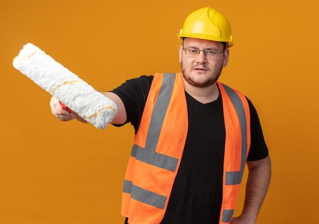 Uomo del costruttore in giubbotto da costruzione e casco di sicurezza che tiene il rullo di vernice che guarda la telecamera con una faccia seria in piedi su sfondo arancione