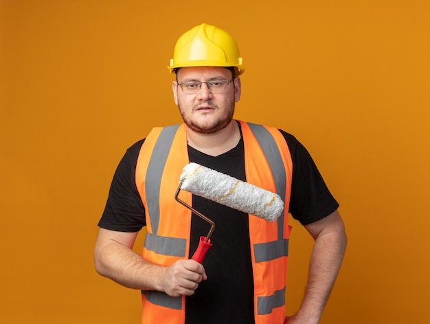 Uomo del costruttore in giubbotto da costruzione e casco di sicurezza che tiene il rullo di vernice guardando la telecamera con faccia seria