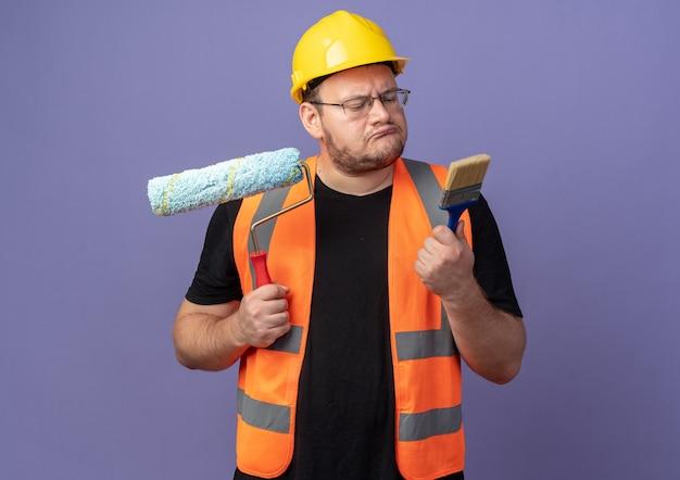 Uomo del costruttore in giubbotto da costruzione e casco di sicurezza che tiene rullo di vernice e pennello che sembra confuso cercando di fare una scelta in piedi su sfondo blu