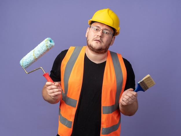 Uomo del costruttore in giubbotto da costruzione e casco di sicurezza che tiene il rullo di vernice e il pennello che sembrano confusi