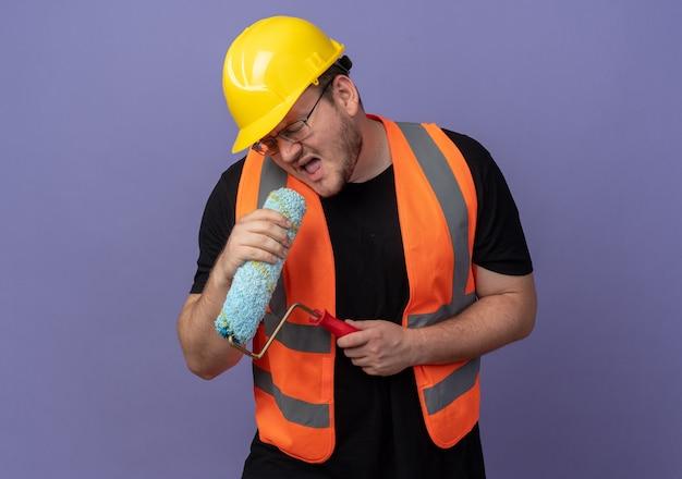 Uomo del costruttore in giubbotto da costruzione e casco di sicurezza che tiene il rullo di vernice usandolo come un microfono che canta divertendosi