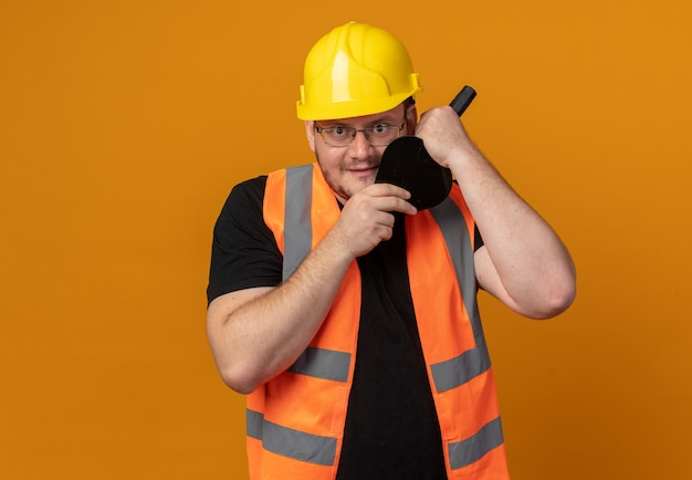 Builder man in construction vest and safety helmet holding putty knife looking at camera smiling slyly