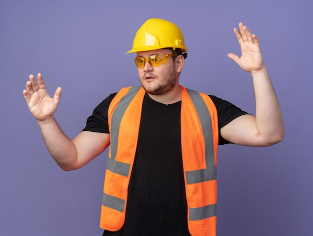 Uomo costruttore in giubbotto da costruzione e casco di sicurezza che guarda da parte sorpreso con le braccia alzate in piedi su sfondo blu