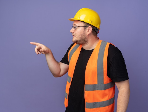 Uomo costruttore in giubbotto da costruzione e casco di sicurezza che guarda da parte con una faccia seria che punta con il dito indice di lato