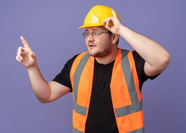 Uomo costruttore in giubbotto da costruzione e casco di sicurezza che guarda da parte preoccupato puntando con il dito indice a qualcosa che sta sopra il blu
