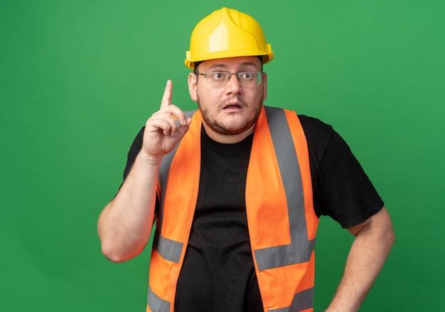 Uomo del costruttore in giubbotto da costruzione e casco di sicurezza che guarda da parte preoccupato che mostra il dito indice in piedi sul verde