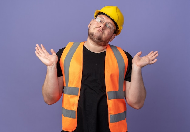 Uomo del costruttore in giubbotto da costruzione e casco di sicurezza guardando la telecamera confusa alzando le spalle senza risposta in piedi sul blu