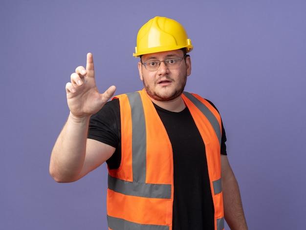 Uomo del costruttore in giubbotto da costruzione e casco di sicurezza che guarda la telecamera che mostra l'avvertimento del dito indice in piedi su sfondo blu