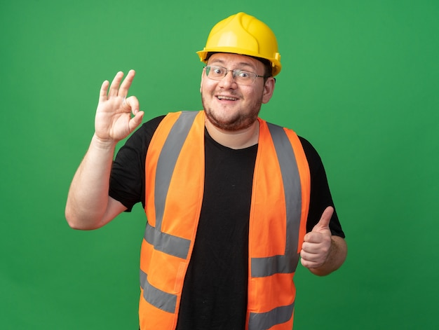 Builder man in construction vest and safety helmet looking at camera smiling cheerfully doing ok sign showing thumbs up standing over green background