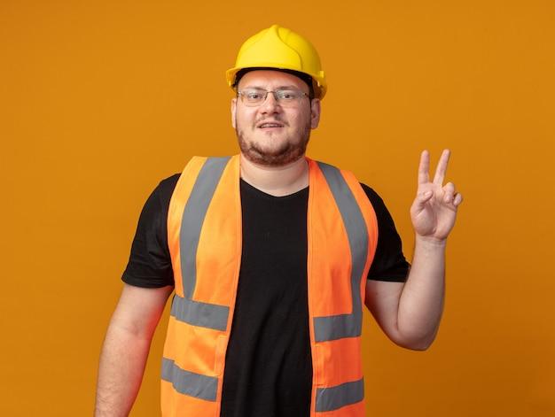 Uomo del costruttore in giubbotto da costruzione e casco di sicurezza che guarda l'obbiettivo sorridente fiducioso che mostra il segno v in piedi su sfondo arancione