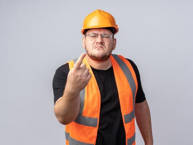 Uomo del costruttore in giubbotto da costruzione e casco di sicurezza che guarda la telecamera con una faccia arrabbiata che fa gesti con la mano mentre discute in piedi sopra il bianco