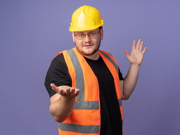 Uomo del costruttore in giubbotto da costruzione e casco di sicurezza che guarda l'obbiettivo con le braccia fuori sorridente fiducioso in piedi su sfondo blu