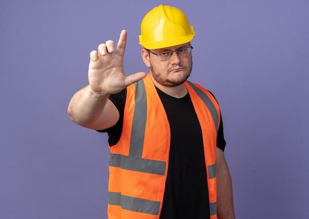 Uomo costruttore in giubbotto da costruzione e casco di sicurezza che guarda la telecamera con una faccia seria che mostra il gesto di avvertimento del dito indice in piedi sopra il blu