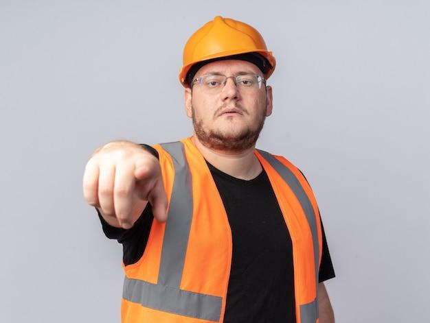 Uomo del costruttore in giubbotto da costruzione e casco di sicurezza che punta con il dito indice alla telecamera guardando fiducioso in piedi su sfondo bianco