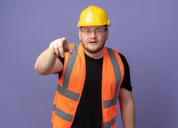 Uomo del costruttore in giubbotto da costruzione e casco di sicurezza che punta con il dito indice alla telecamera guardando confuso in piedi sopra il blu