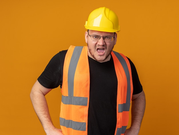 Builder man in construction vest and safety helmet shouting with aggressive expression standing over orange