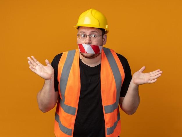 Uomo costruttore in giubbotto da costruzione e casco di sicurezza con nastro adesivo sulla bocca che sembra confuso allargando le braccia ai lati