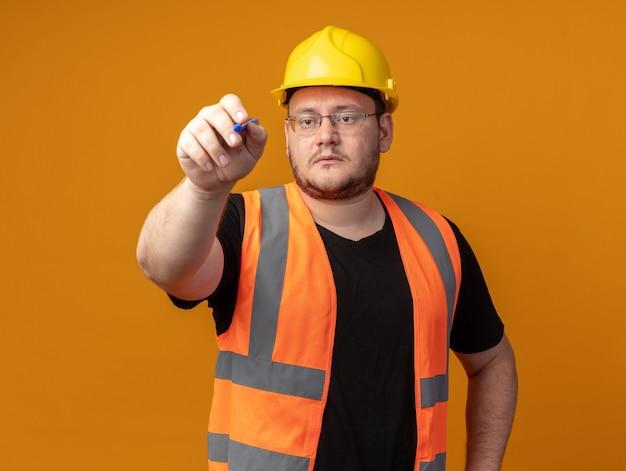 Uomo costruttore in giubbotto da costruzione e casco di sicurezza che scrive con la penna qualcosa con una faccia seria in piedi su sfondo arancione