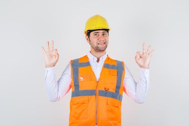 Строитель человек делает нормально жест в рубашке, униформе и выглядит позитивно. передний план.