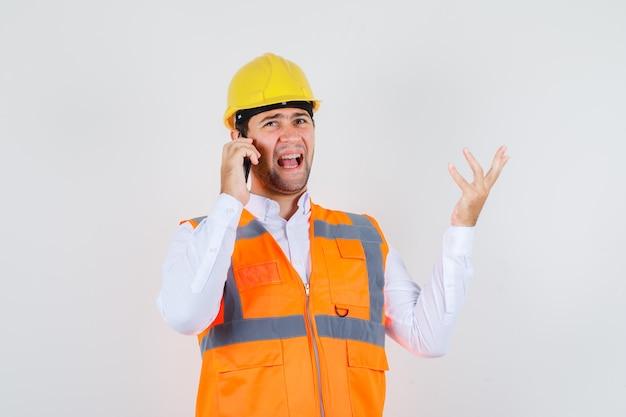 Строитель человек злится во время разговора по смартфону в рубашке, униформе, вид спереди.
