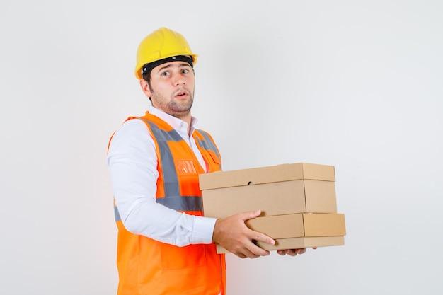 Uomo del costruttore che tiene scatole di cartone in camicia, uniforme e dall'aspetto irresoluto. vista frontale.