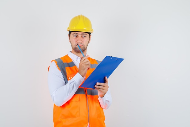 Builder man holding clipboard and pencil in shirt, uniform and looking helpless. front view.