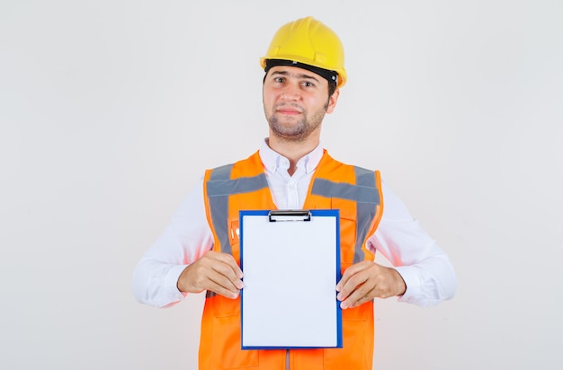 Builder man holding clipboard and smiling in shirt, uniform , front view.