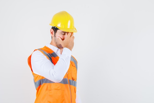 Builder man holding hand on face in shirt, uniform and looking exhausted. front view.