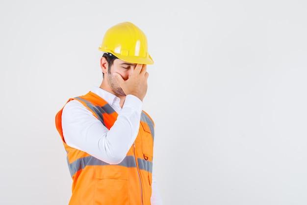 Строитель мужчина держит руку на лице в рубашке, униформе и выглядит измученным. передний план.