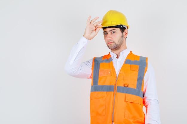 Строитель мужчина держит шлем в рубашке, куртке и выглядит серьезным, вид спереди.
