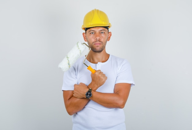 Builder man holding paint roller in white t-shirt, helmet and looking confident, front view.