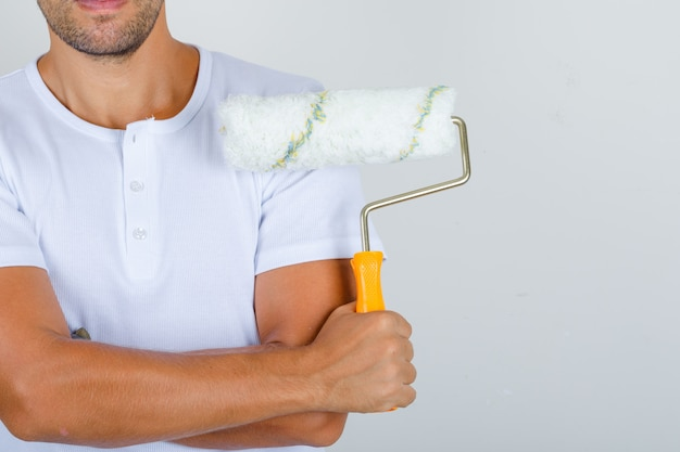 Строитель мужчина держит валик со скрещенными руками в белой футболке, вид спереди.