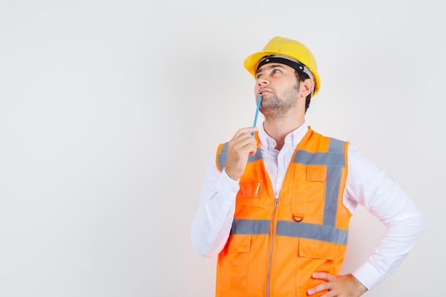 Строитель мужчина держит карандаш возле рта в рубашке, униформе и задумчиво. передний план.