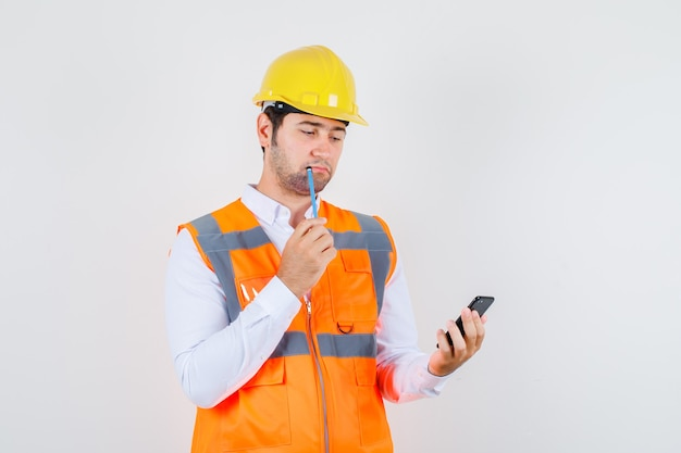 Builder man holding pencil while looking at smartphone in shirt, uniform and looking pensive , front view.